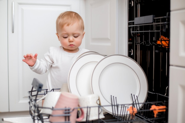 Baby boy en ropa blanca utiliza lavavajillas