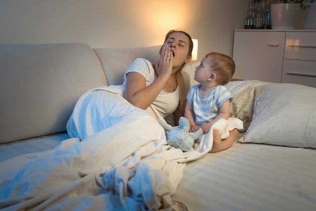 Baby boy sentado en la cama y mirando bostezo madre cansada