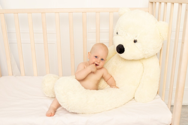 Baby boy sentado en pañales en una cuna con un osito de peluche
