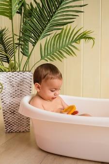 Baby boy sentado en una tina con naranjas en una pared de madera