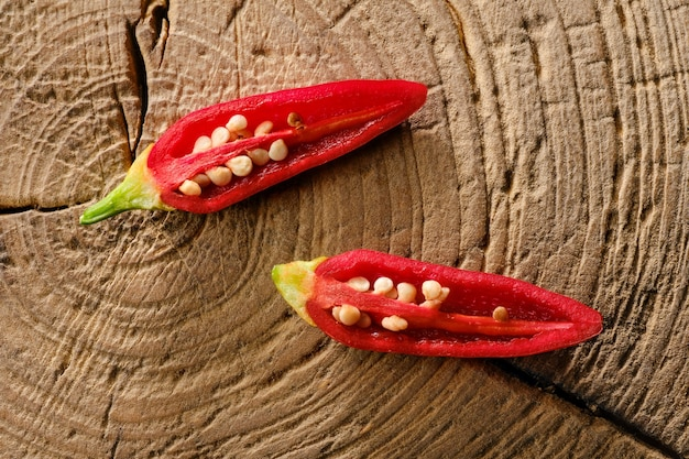 Baby jalapeño pepper cortado en dos mitades sobre mesa de madera