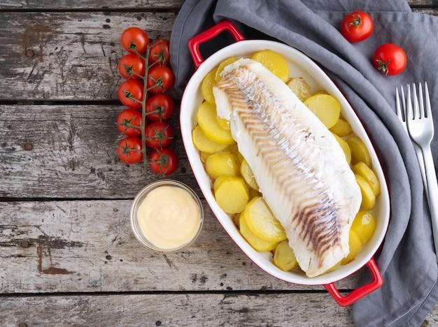 Bacalao al horno con patatas al horno. vista superior, copia espacio.