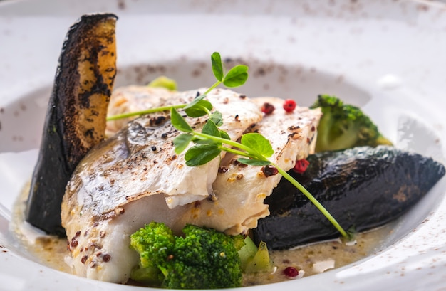 Bacalao filete de verduras en un plato. de cerca