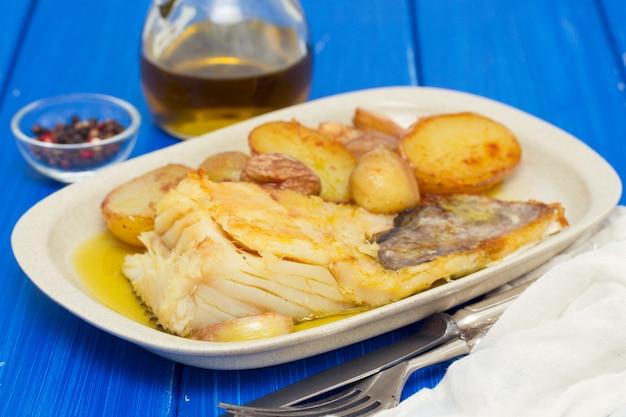 Bacalao frito con castañas y patata en plato blanco