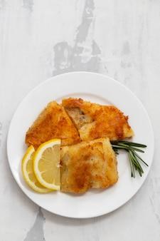 Bacalao frito con limón en plato blanco