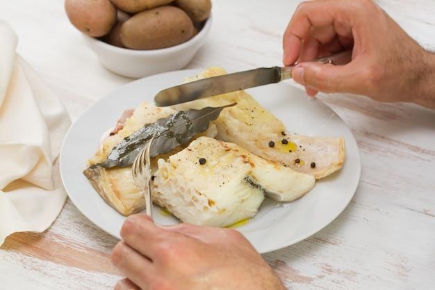 Bacalao hervido con patatas y manos de hombre