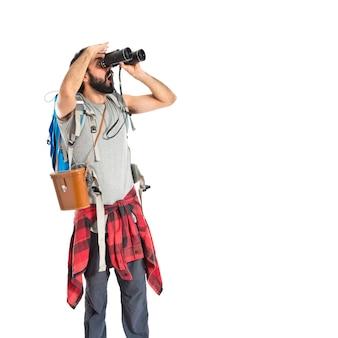 Backpacker con binoculares sobre fondo blanco aislado