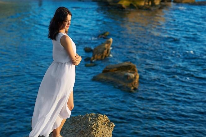 Backview de la chica joven que se coloca en roca en el mar azul del verano.