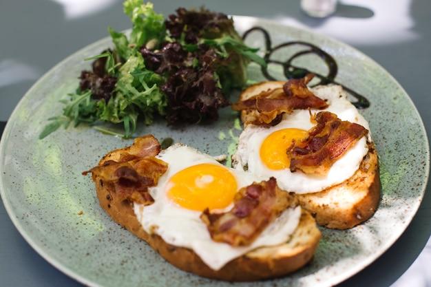 Bacon y huevos fritos sobre tostadas con decocción de lechuga.