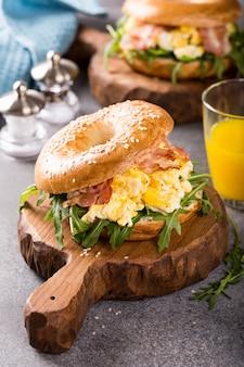 Bagels con huevos revueltos, rúcula y tocino frito