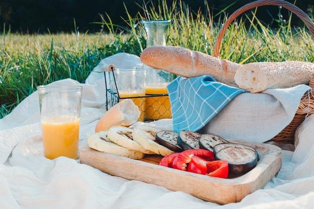 Baguette francés, jugo de naranja y vegetales guisados en un picnic