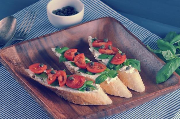 Baguette con queso suave, albahaca, tomates cherry, alcaparras