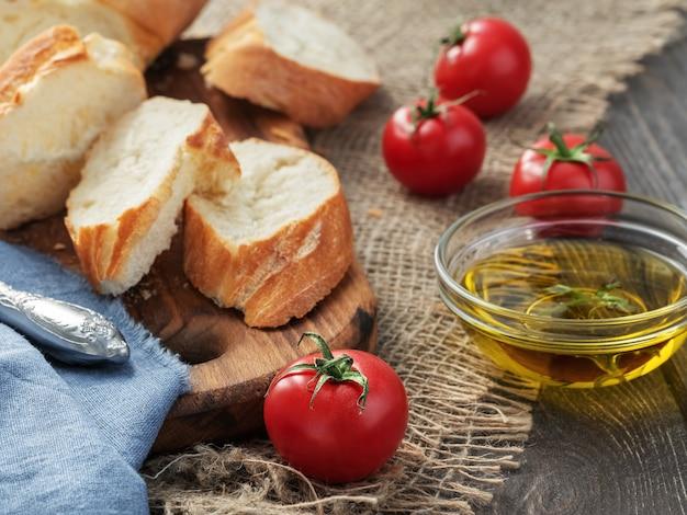Baguette en rodajas frescas, tomates y aceite de oliva, ingredientes para hacer un sandwich, primer plano. fondo de tela áspera