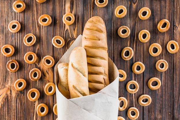 Baguettes envueltas en papel rodeado de panecillos en el fondo de madera