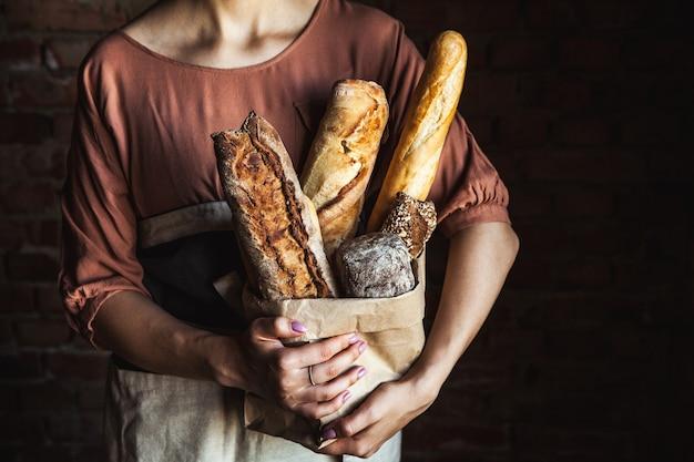 Baguettes francesas en manos femeninas sobre un negro. horneado casero