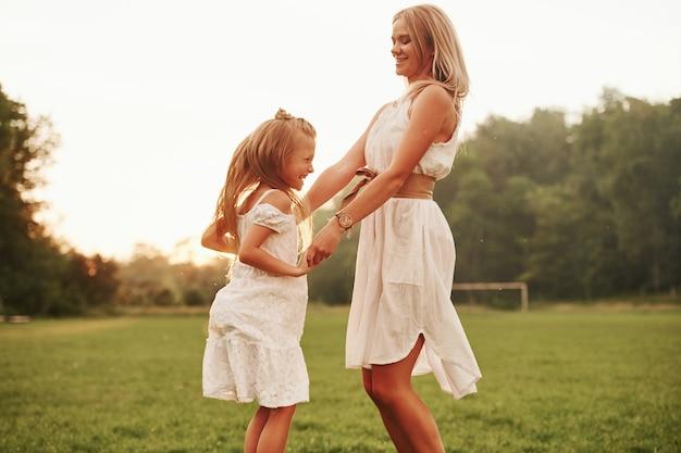 Bailando al sol. madre e hija disfrutando juntos el fin de semana caminando al aire libre en el campo. hermosa naturaleza.