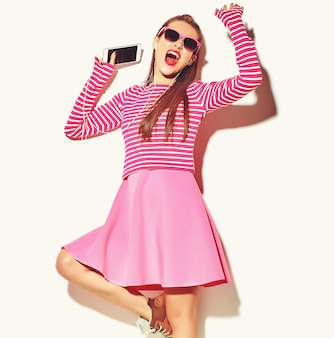 Bailando hermosa feliz linda sonriente sexy morena mujer niña en ropa casual de verano rosa colorida con labios rojos aislados en blanco escuchando música
