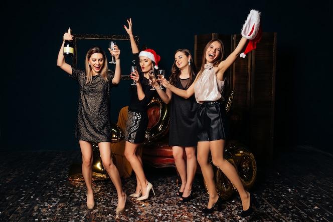 Bailando mujeres hermosas con champán celebrando la navidad