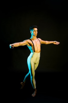Bailarín de ballet clásico masculino realizando en foco