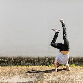 Bailarín de sexo masculino joven que hace handstand contra la pared gris