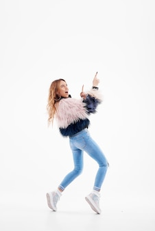 Bailarín feliz joven de la mujer en abrigo de pieles y dril de algodón que presenta en estudio blanco aislado. baile moderno y estilo de vida o hip-hop. muestra un dedo hacia arriba. copiar espacio para texto