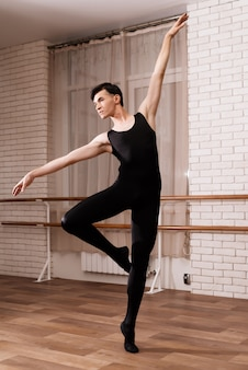 Un bailarín de sexo masculino ensayando en una clase de ballet.