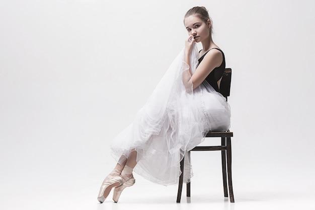 Bailarina adolescente en falda blanca posando en la silla