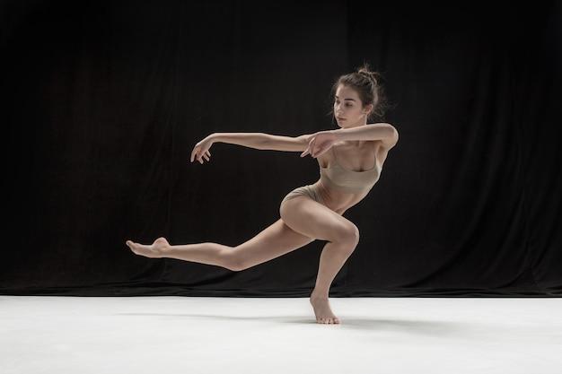 Bailarina adolescente joven en suelo blanco.