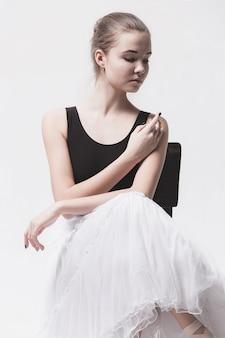 La bailarina adolescente en paquete blanco sentada en una silla