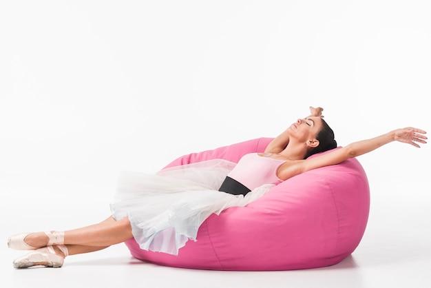 Bailarina agotada joven que se relaja en bolso rosado Foto Premium