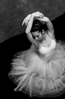 Bailarina de ángulo alto con los brazos cruzados.