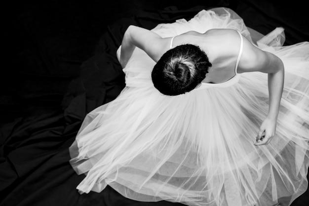 Bailarina de ángulo alto sentada en escala de grises