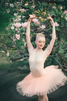 Bailarina bailando al aire libre poses de ballet clásico en tierras de flores