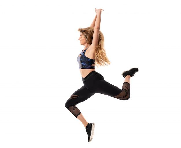 Bailarina bailando sobre pared blanca aislada y saltando