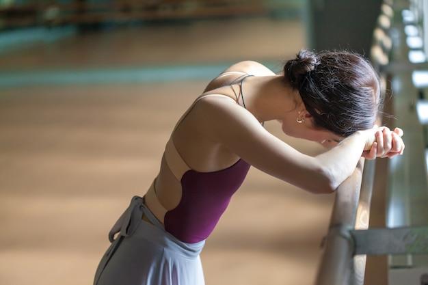 Bailarina de ballet clásico en barre en sala de ensayo