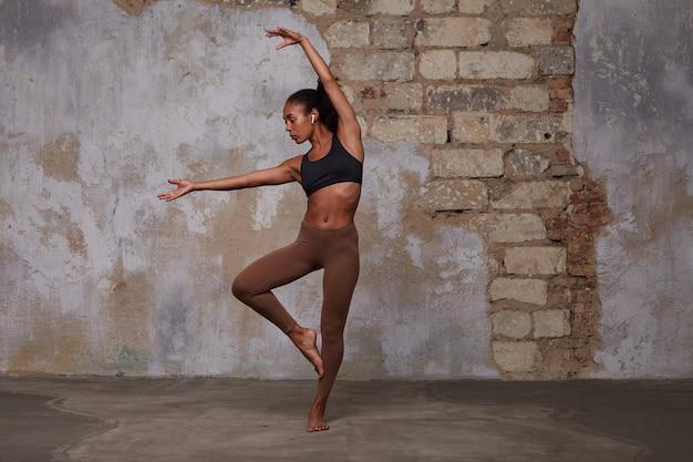 Bailarina de ballet joven flexible de piel oscura con cabello castaño rizado que se extiende sobre la pared de ladrillo, vistiendo top negro deportivo y leggins marrones, con auriculares en los oídos
