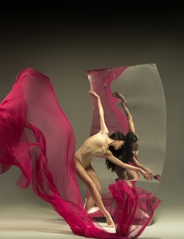 Bailarina de ballet moderno joven y elegante frente a un espejo