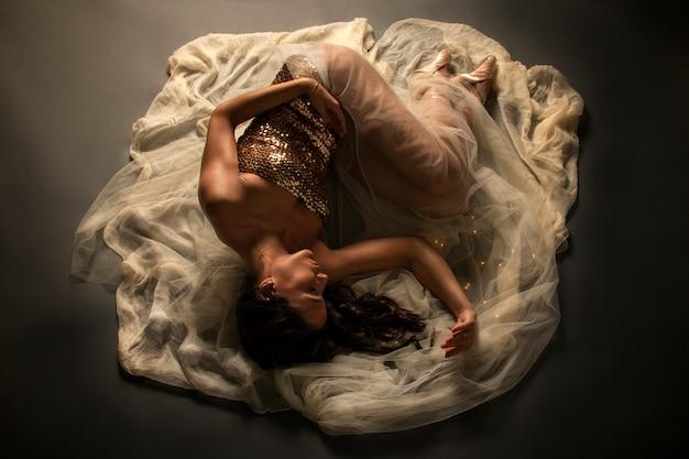 Bailarina de ballet en el suelo sobre un velo
