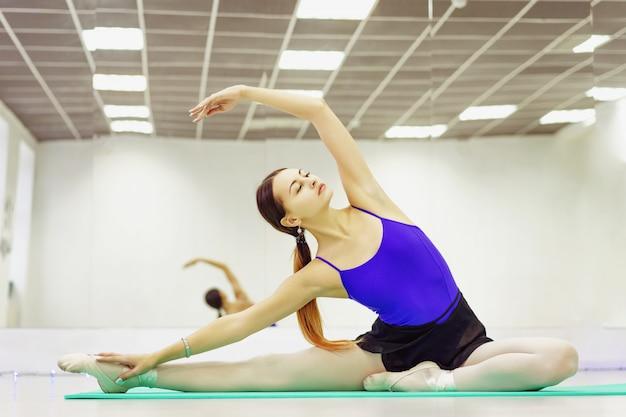 Bailarina de ballet en zapatos pointe calentando en la colchoneta