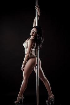Bailarina de barra atractiva mujer sexy actuando sobre fondo gris