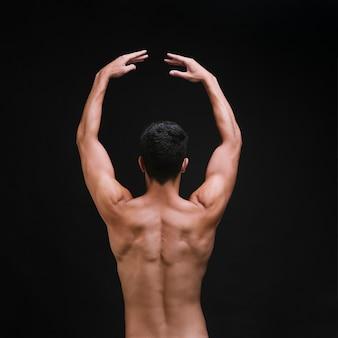Bailarina sin camisa levantando los brazos durante la actuación