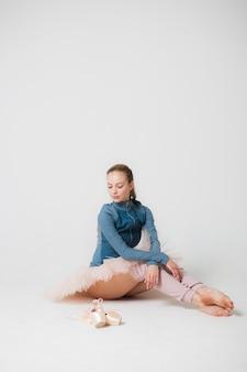 Bailarina cansada está sentada en el suelo sobre un fondo blanco.