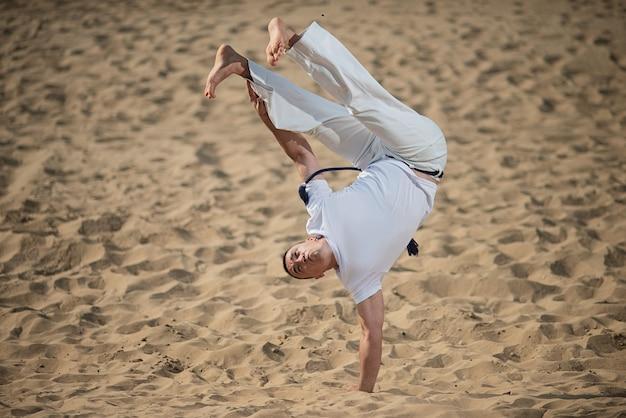 Bailarina de capoeira posando, realizando una parada de manos.