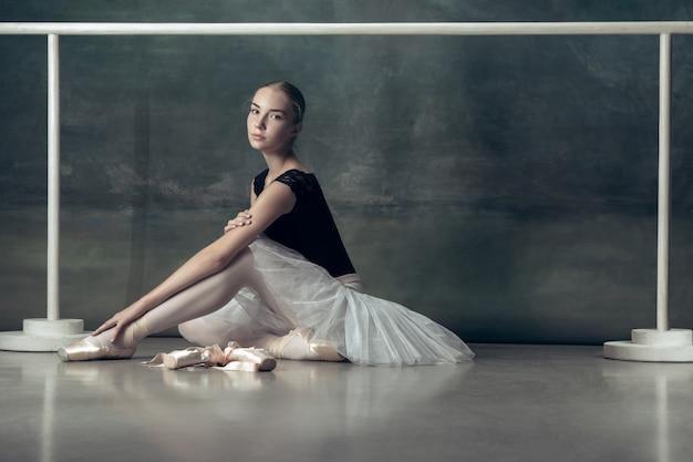 La bailarina clásica posando en la barra de ballet