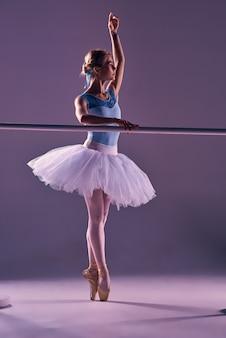 Bailarina clásica posando en la barra de ballet