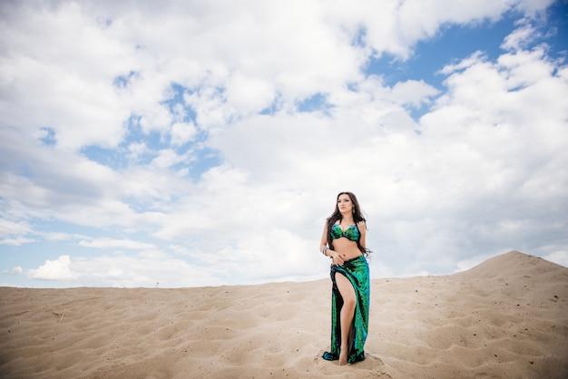 Bailarina de danza del vientre en un traje negro y verde brillante en el desierto contra el fondo de arena.