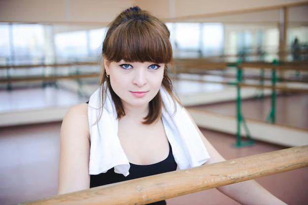 Bailarina descansa después de hacer ejercicios en clase de ballet