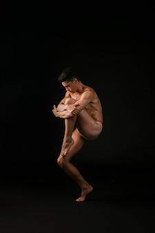 Bailarina desnuda abrazando la rodilla