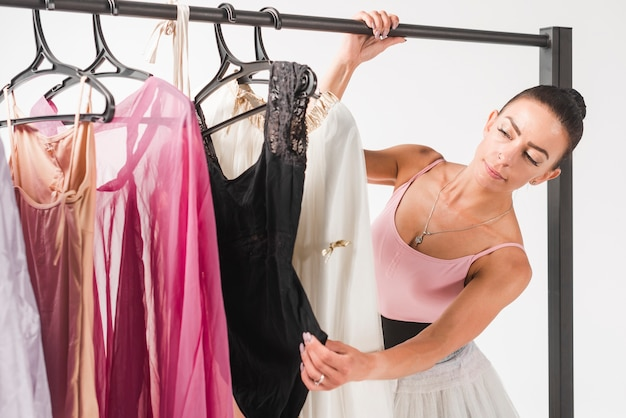 Bailarina eligiendo vestido de perchas