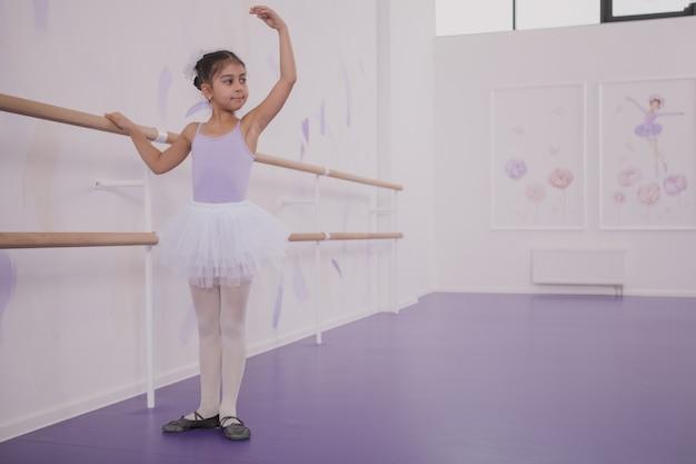 Bailarina encantadora joven haciendo ejercicio en la escuela de baile